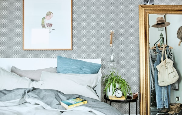 A bedroom with patterned wallpaper, bedding in shades of blue and a gold mirror reflecting a clothes rail.