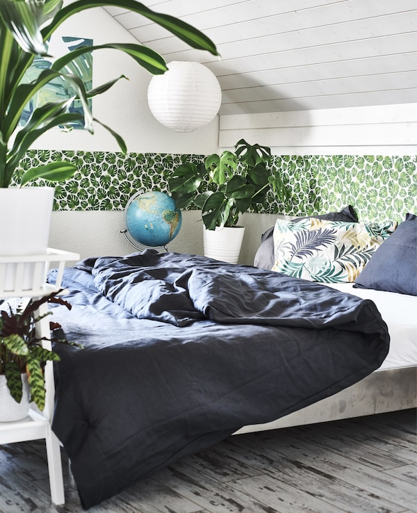 A bedroom with pot plants, green leaf border and dark bedding.