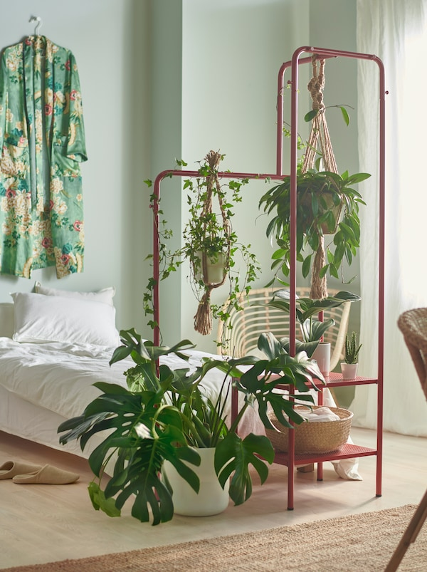 A bedroom with small and large plants at the end of the bed, hanging and standing on a red NIKKEBY clothes rack.