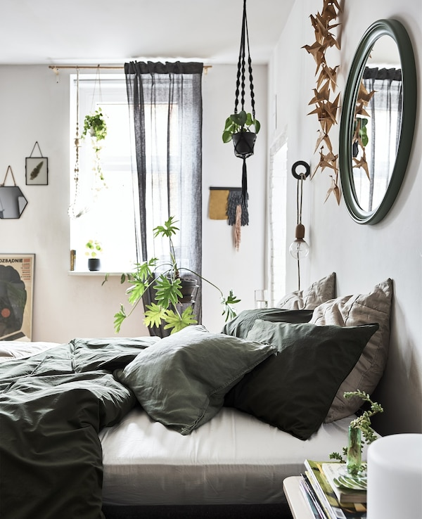 A bedroom with white walls, green bedding and pot plants.