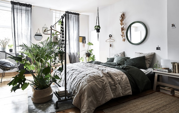 A bedroom with white walls, natural-colored bedding and plants in wicker baskets.