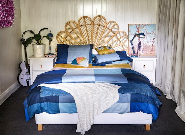 A bedroom with wicker bed head, blue bedding and white bedside tables.