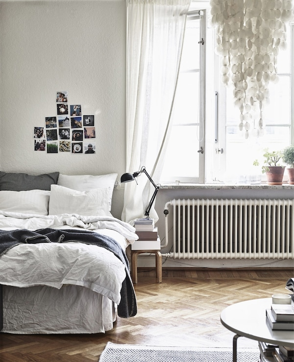 A bedroom with wooden floor and neutral decor.
