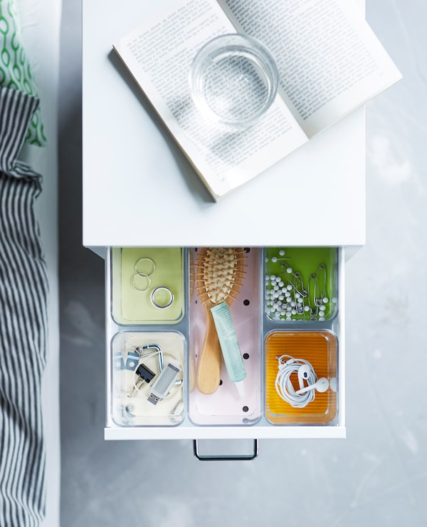 A bedside table drawer that has compartments in it to organise different items
