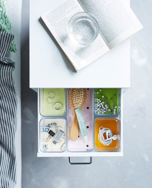 A bedside table drawer that has compartments in it to organize different items