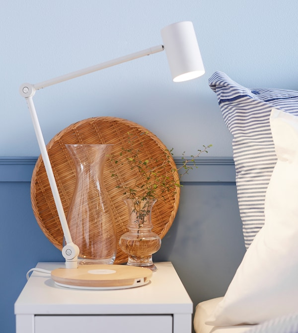 A bedside table is set with a lamp, vase of small flowers and a wicker tray.