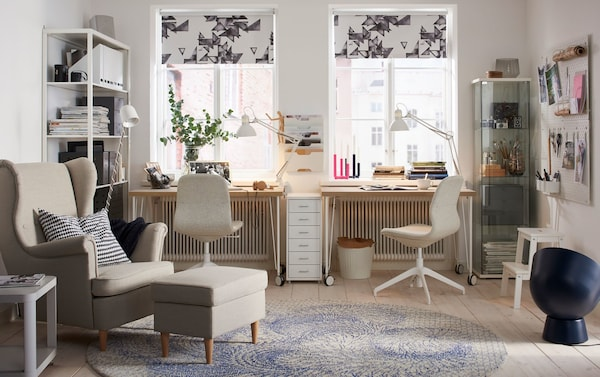 A beige and white home office in a neutral-toned living room. Two desks and two office chairs create two work stations.