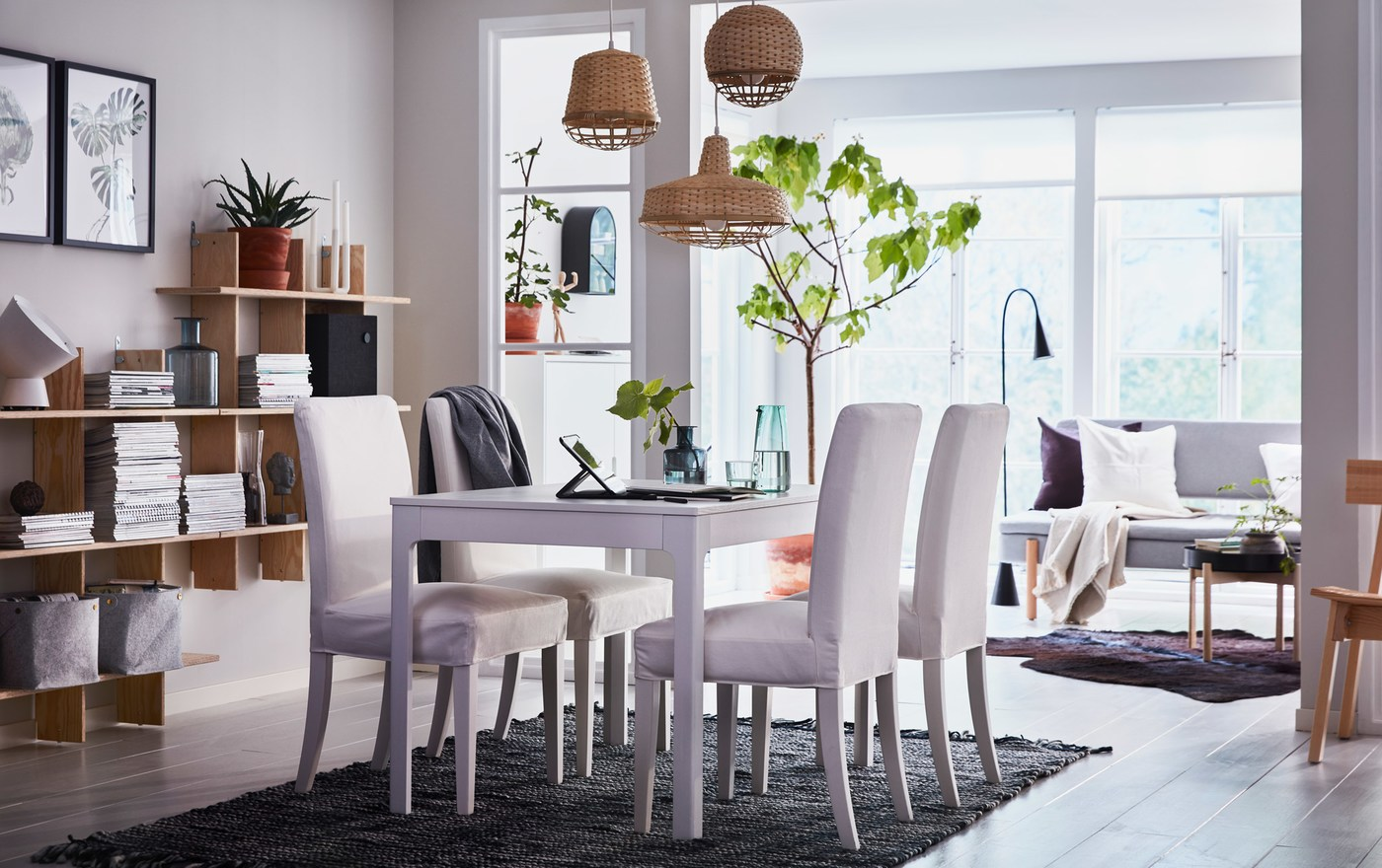 A beige, black and white dining area in an open-plan living space with white upholstered HENRIKSDAL chairs and EKEDALEN extendable table.