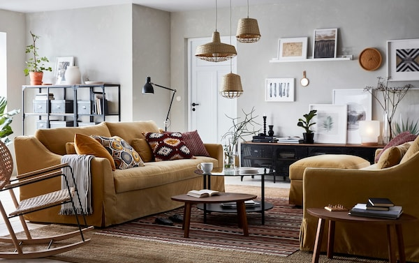 A beige, brown and yellow living room with a pair of FÄRLÖV 3-seat sofas in yellow-beige opposite one another in the centre.