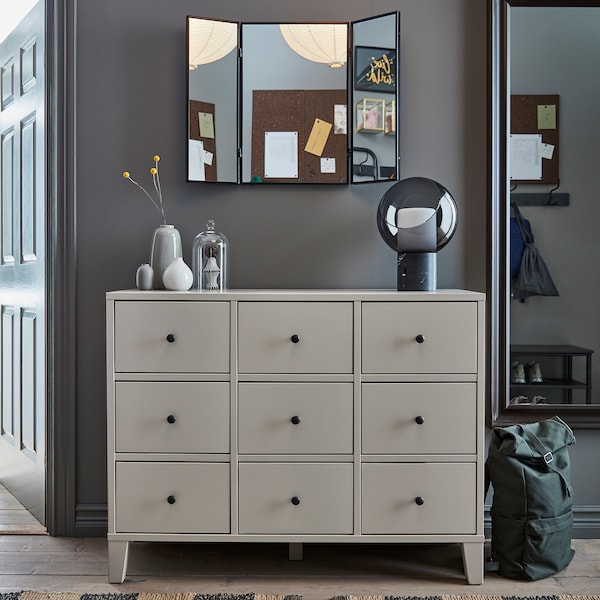 A beige BRYGGJA chest of drawers, a decorative table lamp, a full-body mirror, a wall-mounted mirror and a green backpack.
