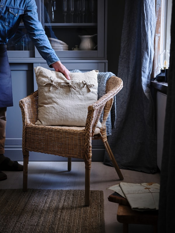 A beige-coloured AINA pillow is placed on a rattan AGEN chair that stands inside a dark blue living room.