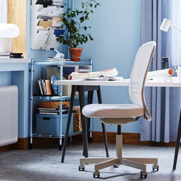 A beige FLINTAN chair in front of a desk.