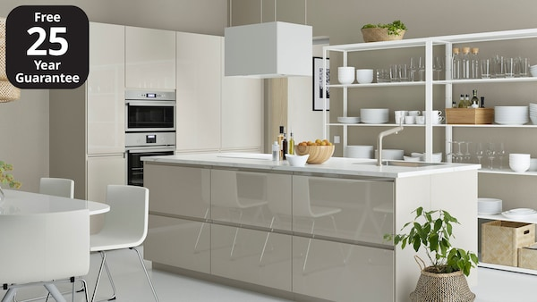 A beige high-gloss IKEA VOXTORP kitchen with island and white worktop.