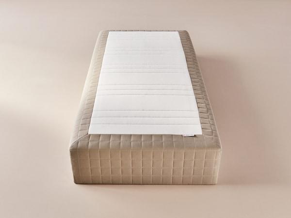 A beige mattress base placed on a beige floor in an empty room.