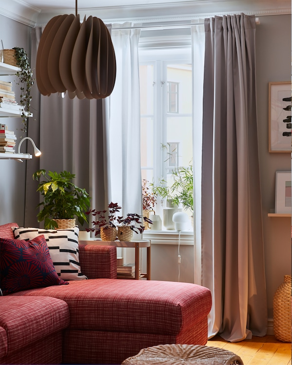 A beige pendant lamp, a red sofa, a footstool in rattan, white and grey curtains and green plants on a window sill.