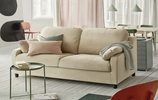 A beige sofa with cushions, books on a mini table in front of it, and a red chair in front of the sofa.