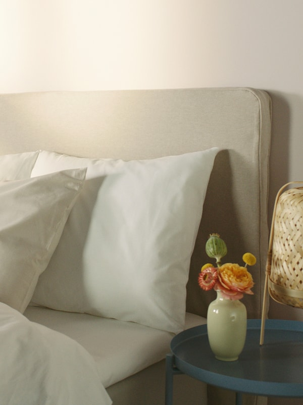 A beige upholstered bed covered in white bed linen, with a round blue table beside it that has a rattan table lamp on it.