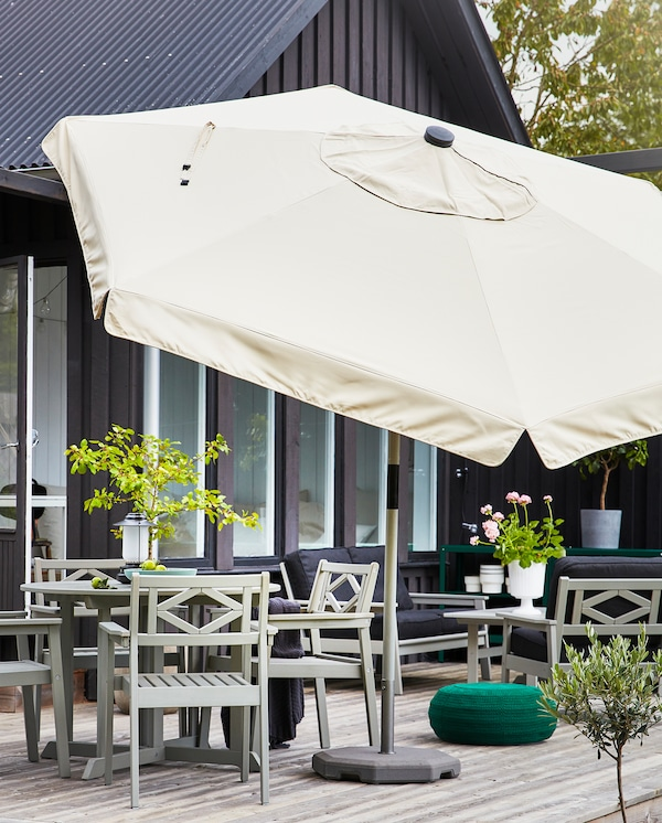 A big, beige parasol is standing next to an outdoor dining area that consists of a grey table and four grey chairs.