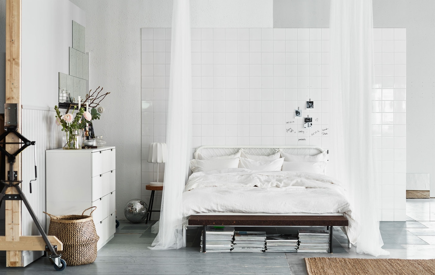 A big white bed low to the floor with crisp white sheets and pillows and sheer white curtains that drape to the floor.