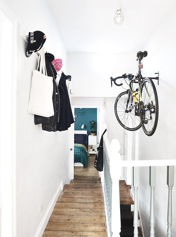 A bike and coats hanging up in a hallway.