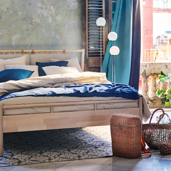 A birch bed with beige and blue bedding, with turquoise and purple block out curtains and woven baskets.