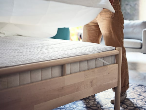 A birch bedframe with a thick beige mattress and white mattress protector. A man is making the bed with white bedding.