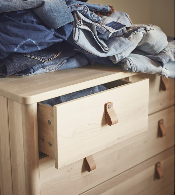 A birch chest of drawers with leather handles.
