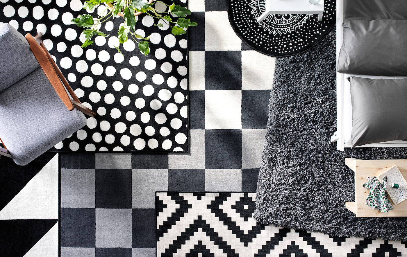 A bird's-eye view of layered black and white rugs in different textures and patterns on the floor of a living room.