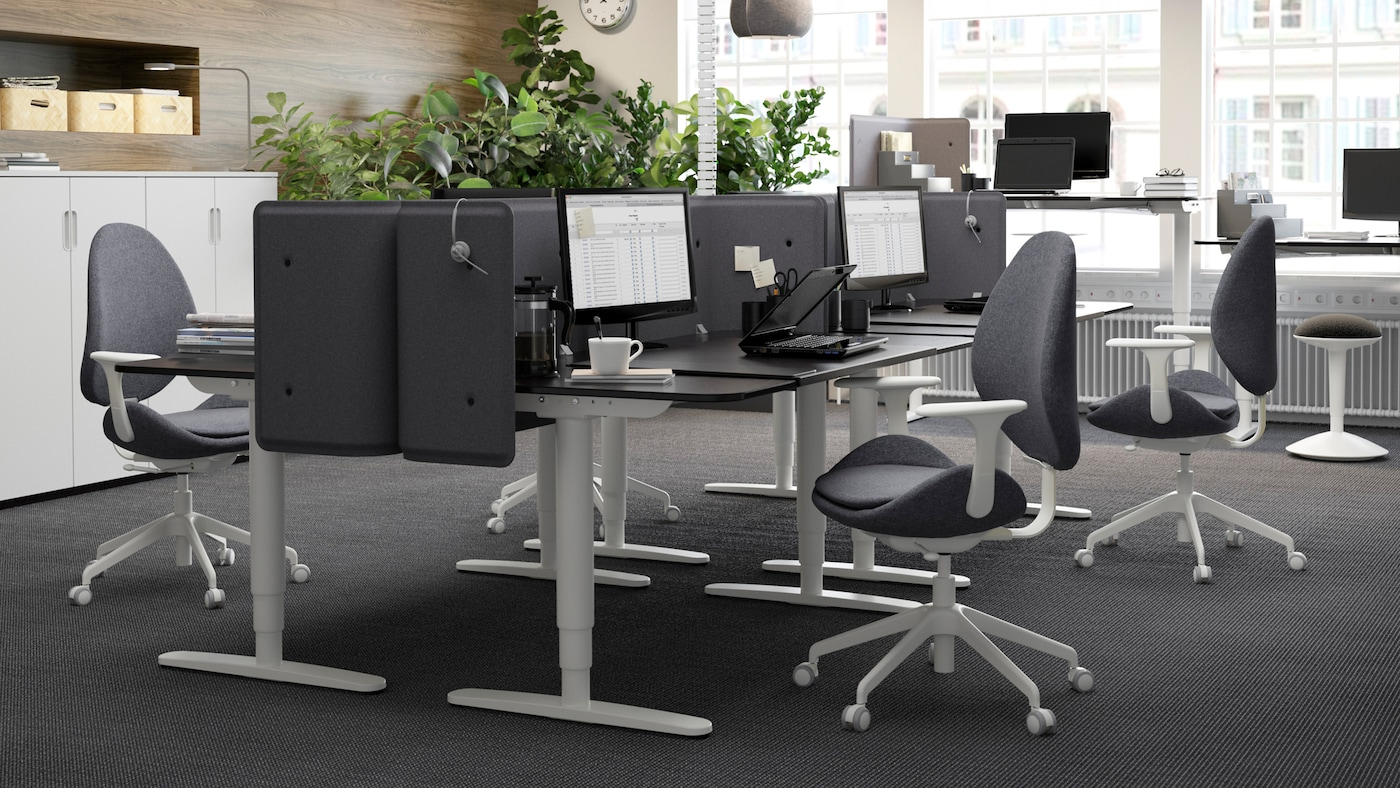 A black and gray office space with black brown BEKANT sit-stand work desks, facing each other to create cubicles.