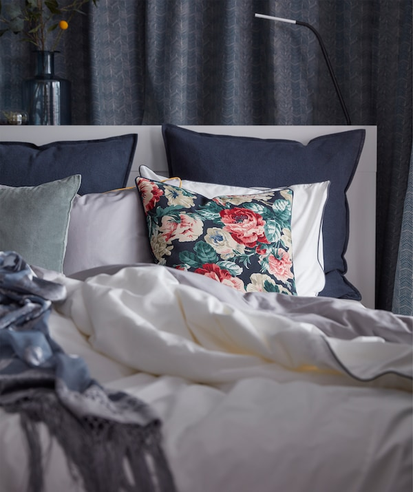 A black and multicolour IKEA LEIKNY cushion cover with a floral print, resting on a bed with other cushions.