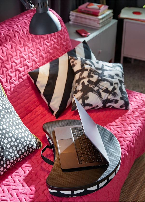 A black and white cushioned IKEA BYLLAN laptop support on a pink sofa amongst grey, black and white cushions.
