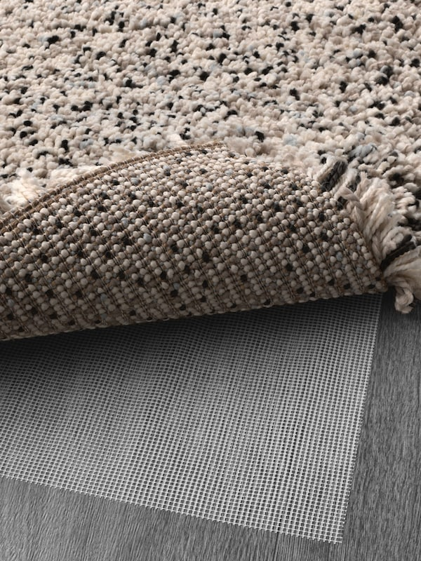 A black and white high pile rug with the corner lifted to show anti-slip mesh