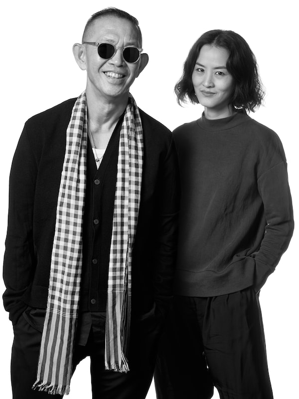 A black-and-white image of a man and a woman known as Thai designers Greyhound Original in front of a white background.