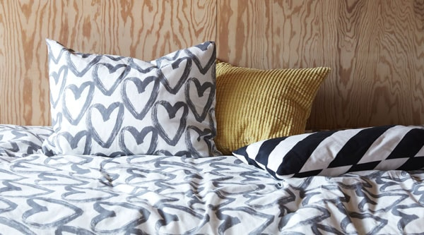 A black and white LYKTFIBBLA duvet cover and pillowcase against a wooden background.