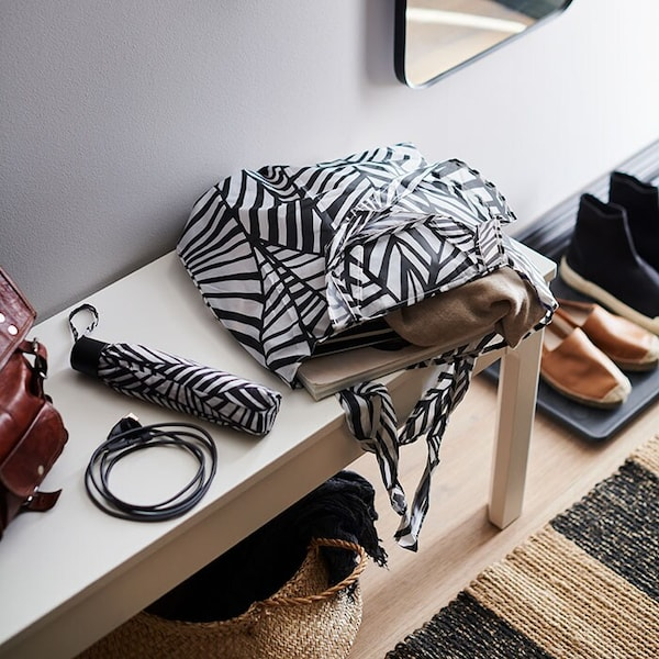 A black and white patterned bag, placed on an entryway bench.