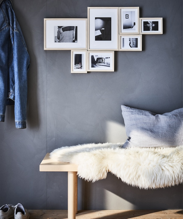 A black and white photo display hanging on a grey wall above a bench covered in a sheepskin.
