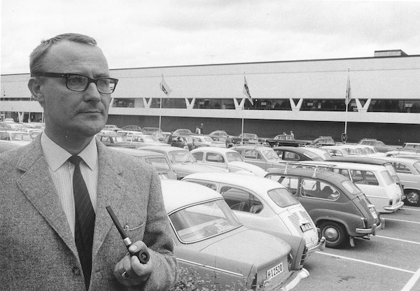 A black and white photo of a young Ingvar Kamprad standing in the parking lot outside of an IKEA store while smoking a pipe.