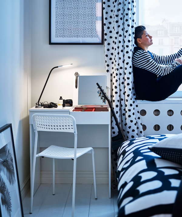 A black and white polka dot bedroom scheme, plus a white desk, chair and painted floor, with a woman sitting in the window.