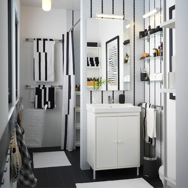 A black and white small bathroom with a white wash basin, striped towels, and a striped shower curtain.