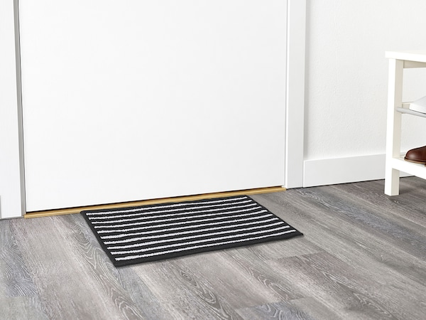 A black and white striped door mat on a gray wooden floor in front of a white doorway.