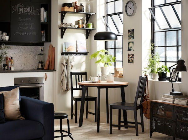 A black and white styled kitchen with an IKEA GAMLARED small round table and two black chairs in the corner.