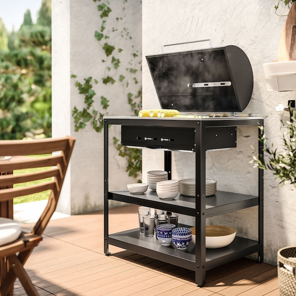 A black barbecue on a stand holding blue and white dishes.