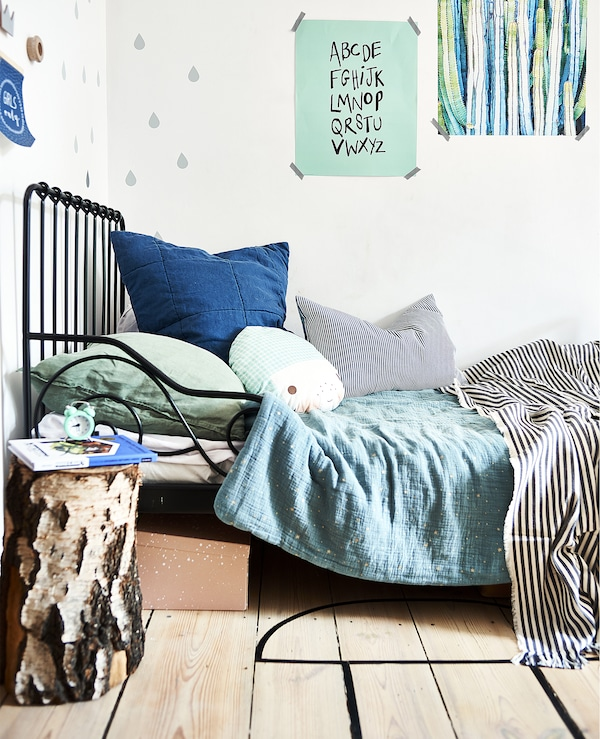 A black bed frame with green and blue bedding and posters on the wall.