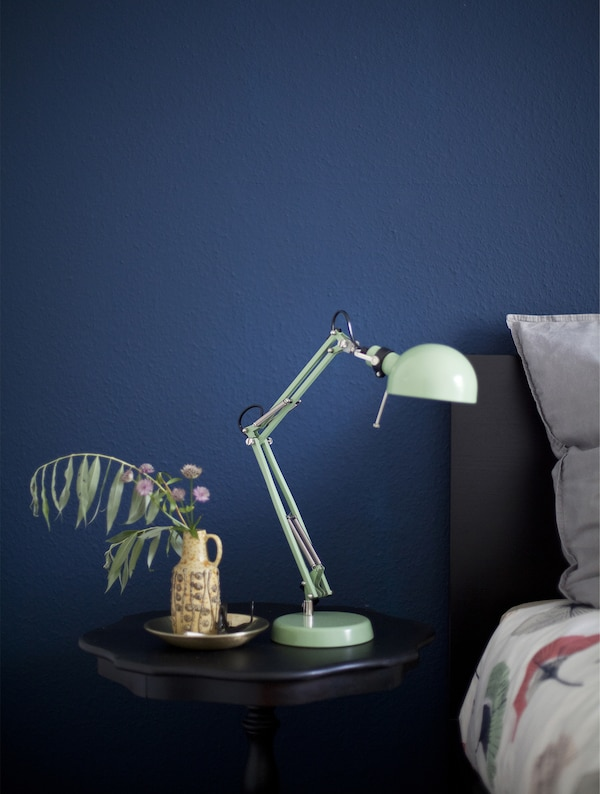 A black bedside table and mint green lamp against a dark blue wall.