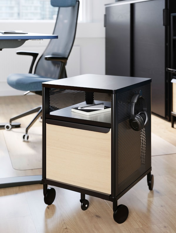 A black BEKANT storage cabinet on castors with a notebook and headphones on it, in front of a blue JÄRVFJÄLLET office chair.