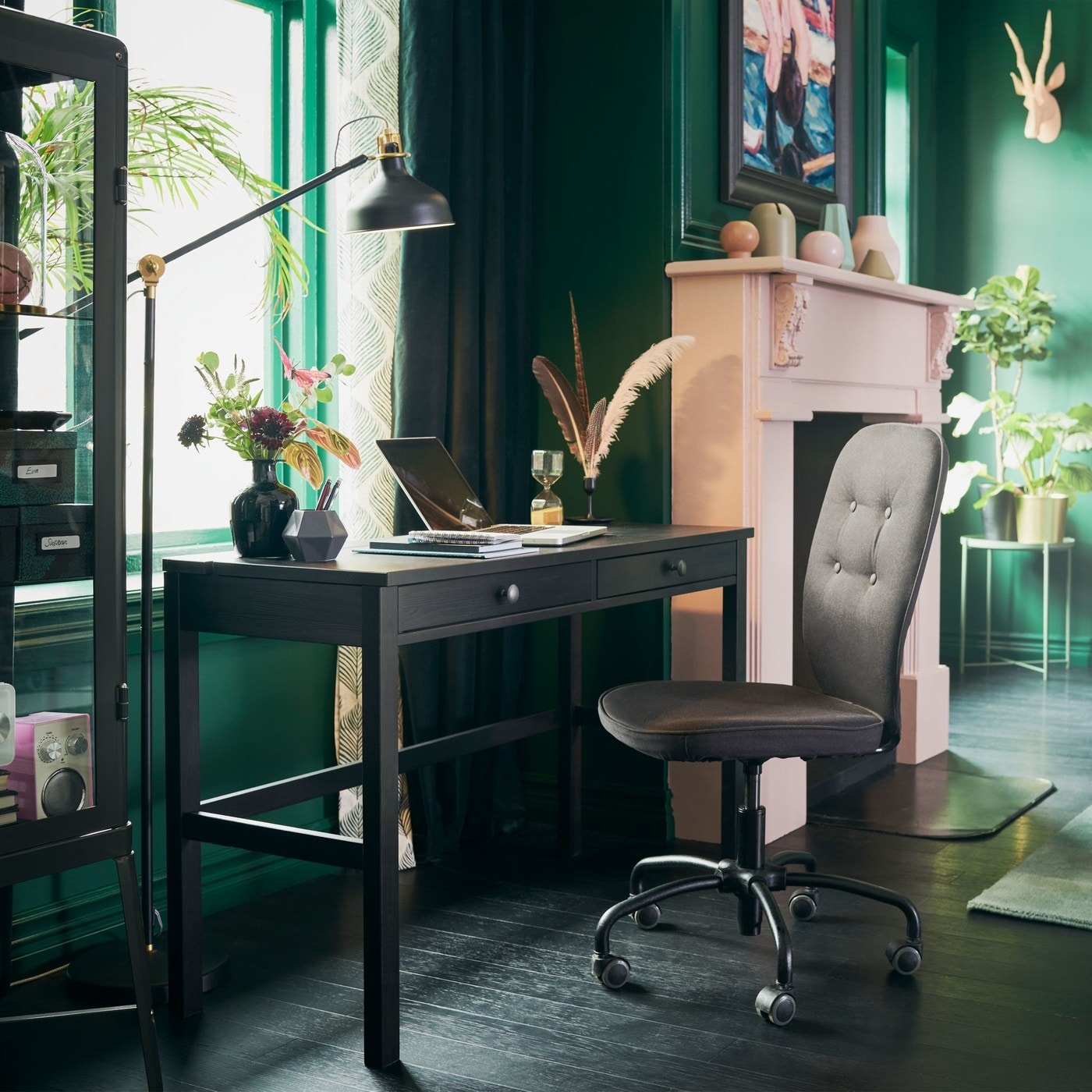 A black brown HEMNES work desk by the window in a sitting room with green walls and a pink fireplace.