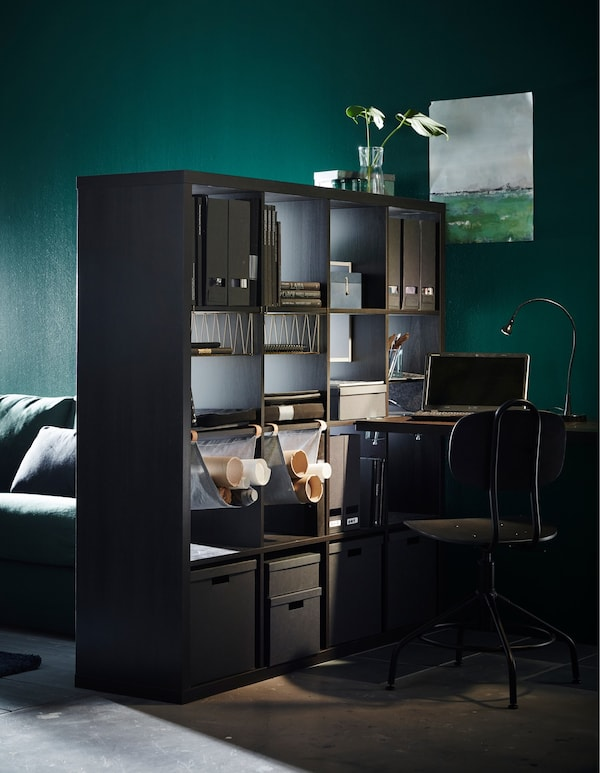 A black-brown IKEA KALLAX shelving unit being used as a room divider to create a separate workspace in the living room.