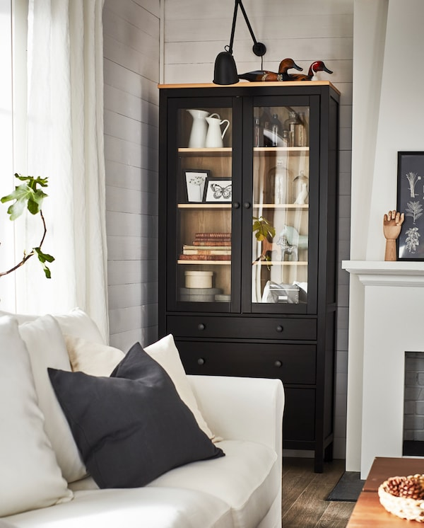 A black-brown/solid pine glass-door cabinet with decorative items, a black wall lamp above and a white sofa in front.