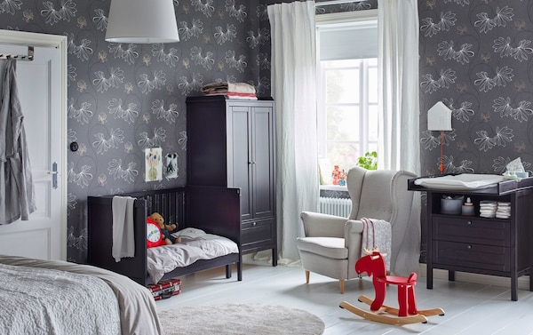 A black brown SUNDVIK cot, wardrobe and nappy changing table in the corner of a large adult bedroom with grey wallpaper.
