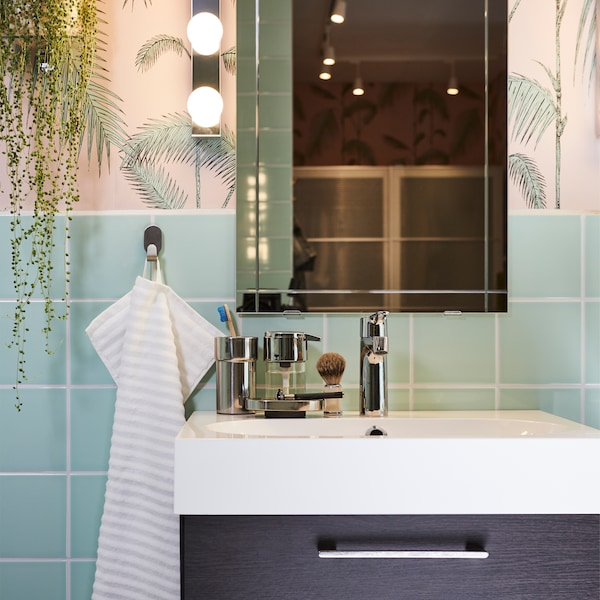 A black-brown wash stand, a white wash basin, a mirror and lighting by it, and a striped towel in a pink/green bathroom.
